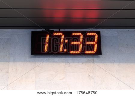 Large discrete electronic clock on the wall of the building show time outdoors close-up view