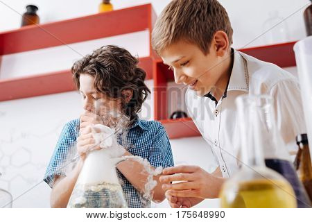 In the middle of experiment. Nice brunette positive boy holding a chemical flask and coughing while carrying out an experiment with his friend