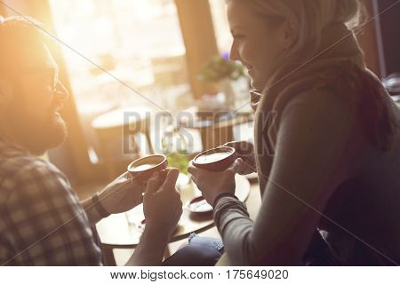 Young couple in love sitting in a cafe drinking coffee having a conversation and enjoying the time spent with each other. Focus on the right coffee cup