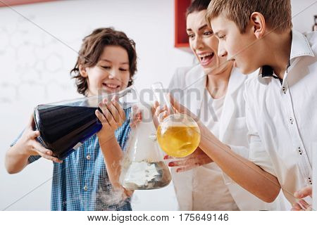 Interesting experiments. Cute happy nice boy holding a big flask and pouring liquid in the other flask while taking part in the experiment