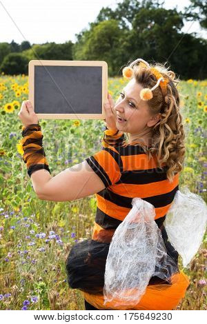 A woman dressed as a bee holds up a sign