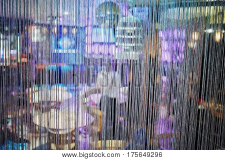 Interior of cafe through semitransparent curtain made of cords.