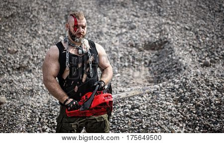 marauder With a red chain saw in his hands and a chain around his neck