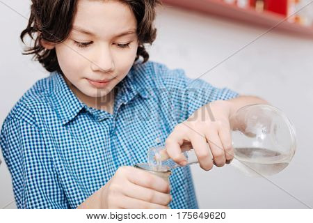 Interested in the activity. Clever nice young boy holding chemical flasks and mixing liquids while wanting to see what will happen