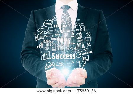 Businessperson holding abstrat business sketch on dark background. Leadership concept