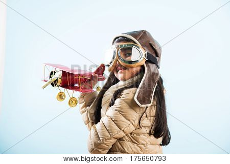 Happy Indian or asian girl kid playing with toy metal airplane against winter sky background - Kid and flying or ambition concept