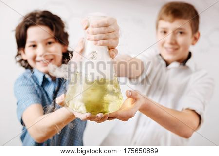 We love chemistry. Cheerful delighted nice boys smiling and holding a chemical flask while showing it to you