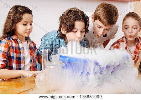 Favourite subject. Intelligent smart positive children standing around the washbowl and blowing on the fume while attending a chemistry lesson
