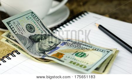 US dollars bills and a cup of coffee. Currency foreign exchange. Business and Financial or money management for investments.
