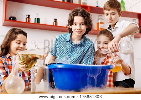 What will happen. Curious smart positive children standing around a washbowl and pouring chemical liquids there while enjoying themselves