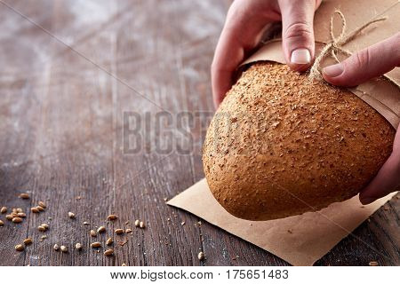closeup of men hands with light bread and flour of white color. Bread in the kitchen paper and decirative rope. Brown background. Wooden table with flour and wheat. Baker and tasty.