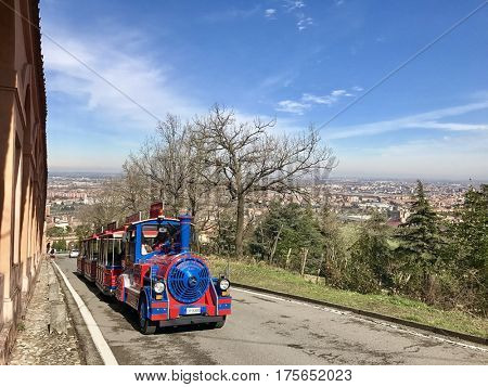 BOLOGNA - MARCH 7, 2017: A Tourist Train climbs the Colle della Guardia alongside the Portico di San Luca towards the San Luca Sanctuary in Bologna, Italy.
