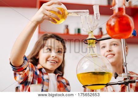 Well equipped laboratory. Selective focus of a modern chemical equipment being used by pretty happy cute girls while experimenting