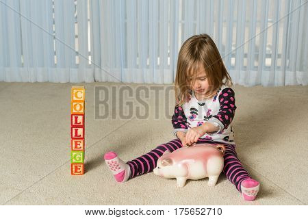 Young girl on floor of home saving money in a piggy bank for college educational expenses in the future
