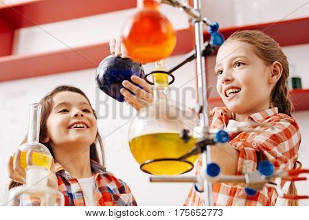 School scientific club. Cute joyful nice girls using scientific equipment and carrying out an experiment while being in the school lab