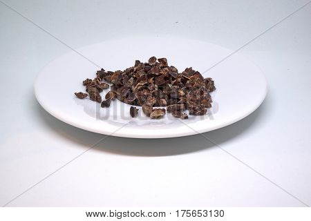 cacao nibs on a plate isolated on white background