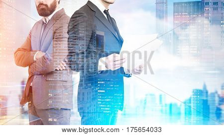 Close up of an unrecognizable business duo. One businessman is holding documents his partner is standing with crossed arms. Blue city. Double exposure mock up toned image