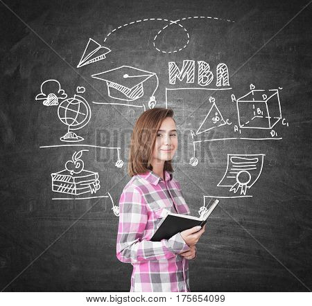 Portrait of a geek girl holding a black book and standing near a chalkboard with an MBA sketch on it.