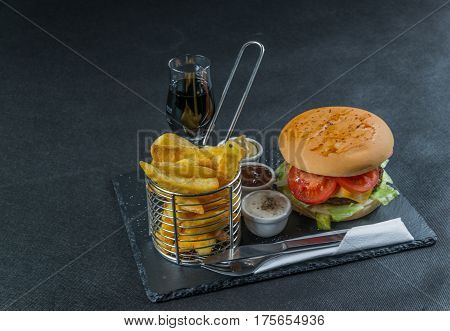 Left Side View On A Flame Grilled Double Stack Cheeseburger, Lettuce, Tomato, With Three Sauces, Chi