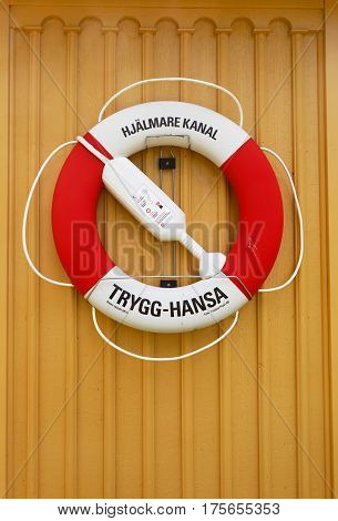 Arboga Sweden - August 5 2016: One red and white lifebuoy marked with Trygg-Hansa hanging on a yellow wall at the Gravudden locks in the Hjalmare channel.