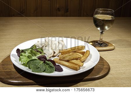 Healthy low calorie chicken meal with salad and wine. Slimmer's portion of organic free range chicken baby lettuce and spinach leaf salad and potato chips - fries. With a glass of white wine.
