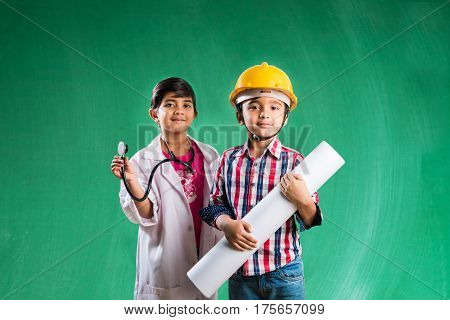 Kids and education concept - Small indian boy and girl posing in front of Green chalk board in engineers fancy dress and doctor costume with stethoscope, wanna be engineer or doctor