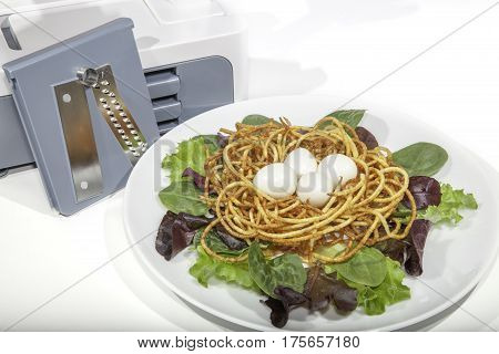 Vegetable spiralizer with healthy organic spiralized meal. Boiled quail eggs in potato nest with baby leaf salad.