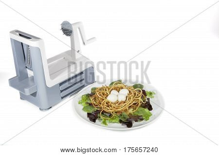 Vegetable spiralizer with healthy spiralized meal of boiled quail eggs in a fried potato french fries nest. Served with baby leaf green salad White background copy space.