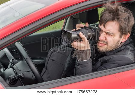 Stalker Or Paparazzi Is Taking Photo With Camera From Car.