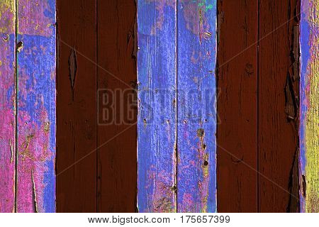Years of colorful paint peeling from vertical timber boards. Multiple layers of paint being stripped from wood. A useful striped background abstract image.