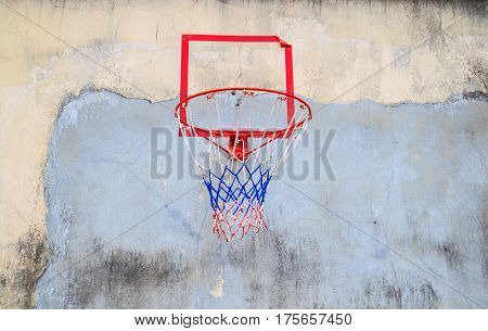 Basketball hoop cling to old wall of house.
