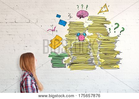 Girl with drawn paperwork pile on brick wall. Workload concept