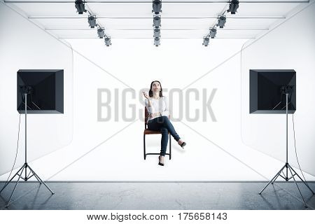 Attractive woman sitting on chair in modern photo studio with professional lighting equipment. 3D Rendering