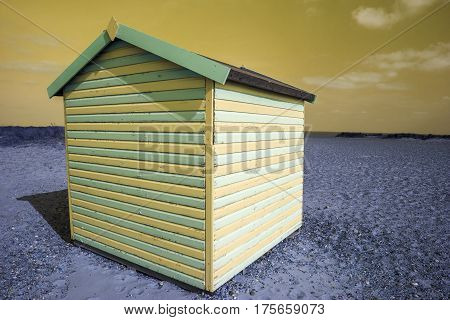 Fantasy green and yellow striped beach hut. Color manipulated image of a vibrant beach hut on blue soil against a yellow sky. Representing space tourism and a vacation on another planet.