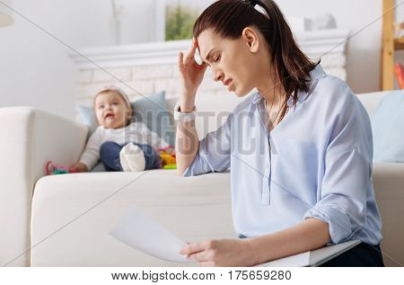 How can I handle it. Tired ambitious business lady having a headache after working long hours and trying looking after her child simultaneously