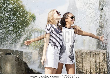 Teenagers Concepts. Two Teenage Girfriends Embracing Together. Posing Against Fountain in Park Outdoors. African American Model and Caucasian Blond Model.Horizontal Image Composition