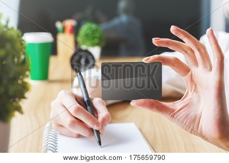 Girl showing black card and writing in spiral notepad placed on wooden office desktop with coffee cup clock plant and other items. Mock up Ad concept