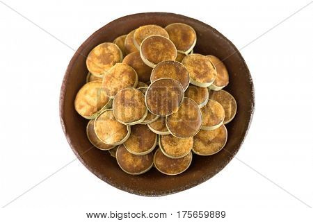 Clay bowl full of Jaggery sugar made of Asian Palmyra Palm sap filled in slices of small dried palm leaves, isolated on white background