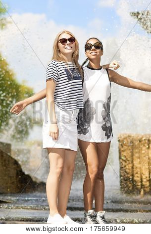 Teenagers Concepts. Two Funny and Laughing Teenage Girfriends Embracing Together. Posing Against Fountain in Park Outdoors. African American Model and Caucasian Blond Model. Vertical Image Composition