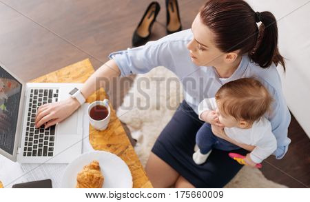 Active start. Brilliant strong caring woman looking through an article using her laptop while having a brunch in company of her daughter