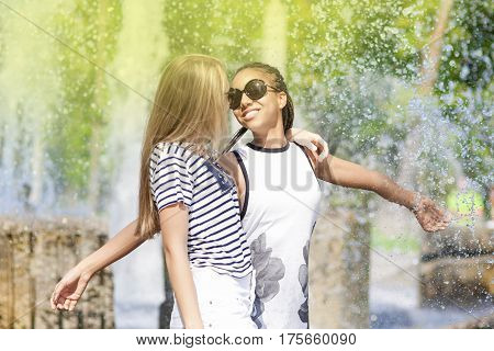 Portrait of Two Funny Teenage Girfriends Embracing Together Against Fountain in Park Outdoors. African American Model and Caucasian Blond Model. Horizontal Image Composition