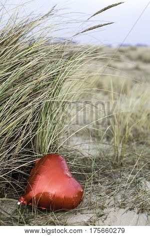 A red heart balloon left on the beach. Symbolic of a holiday romance; lost love; or sex on the beach etc.