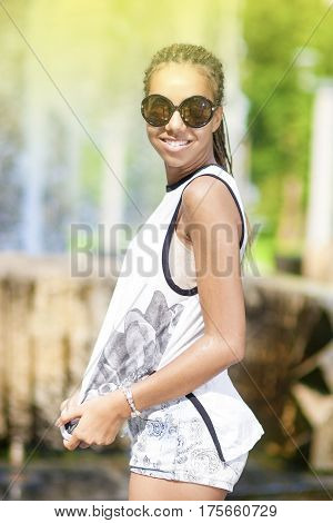 Teenager Lifestyle Concepts. Happy Smiling Young African American Teenager Girl With Plenty of Dreadlocks Posing in Park Outdoors.Vertical Image Orientation
