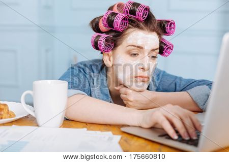 Nothing interesting. Wonderful emotional cute lady browsing through the Internet while sitting at the table wearing hair curlers and mask