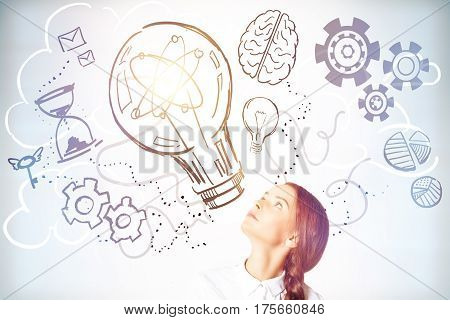 Pretty girl looking up at abstract lamp cogs and brain sketch. Creative idea concept