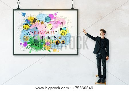 Young businessman with business drawing in frame. Concrete background. Success concept