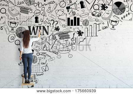 Back view of young woman standing on stool and drawing creative business sketch on brick wall. Leadership concept