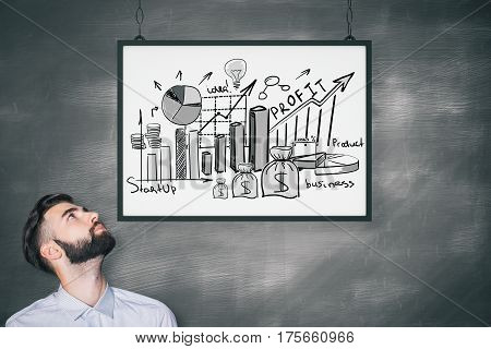 Young businessman with business doodle in frame. Chalkboard background. Success concept