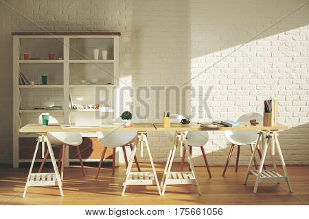 Clean office interior with items on shelves laptop on table other items equipment and sunlight