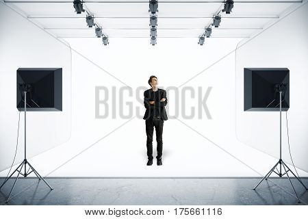 Handsome young man in suit standing in modern photo studio with professional lighting equipment. 3D Rendering